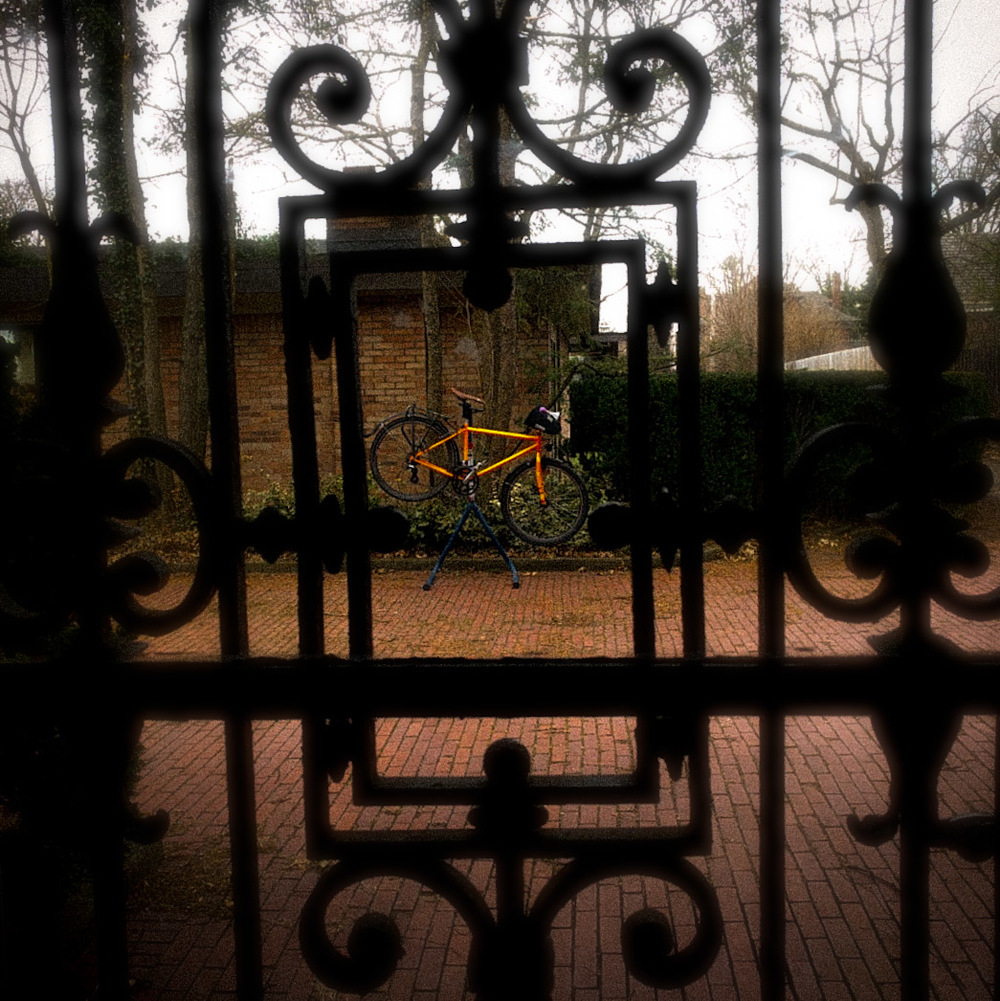 photo of my ridiculously orange bike on a work stand in the driveway, framed through an ornamental wrought-iron door