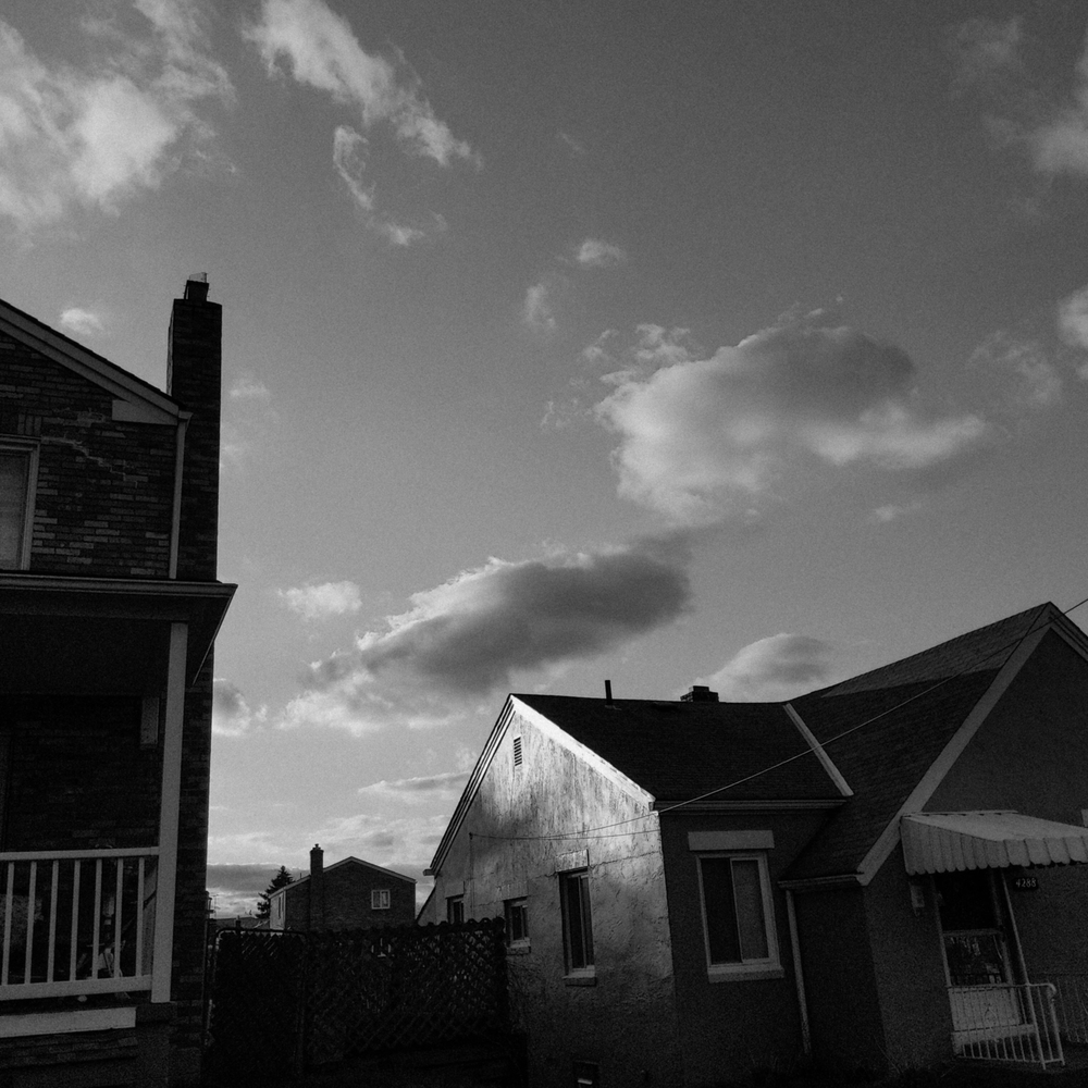 black and white photo of the side of a house, with other houses visible, and a flat sky