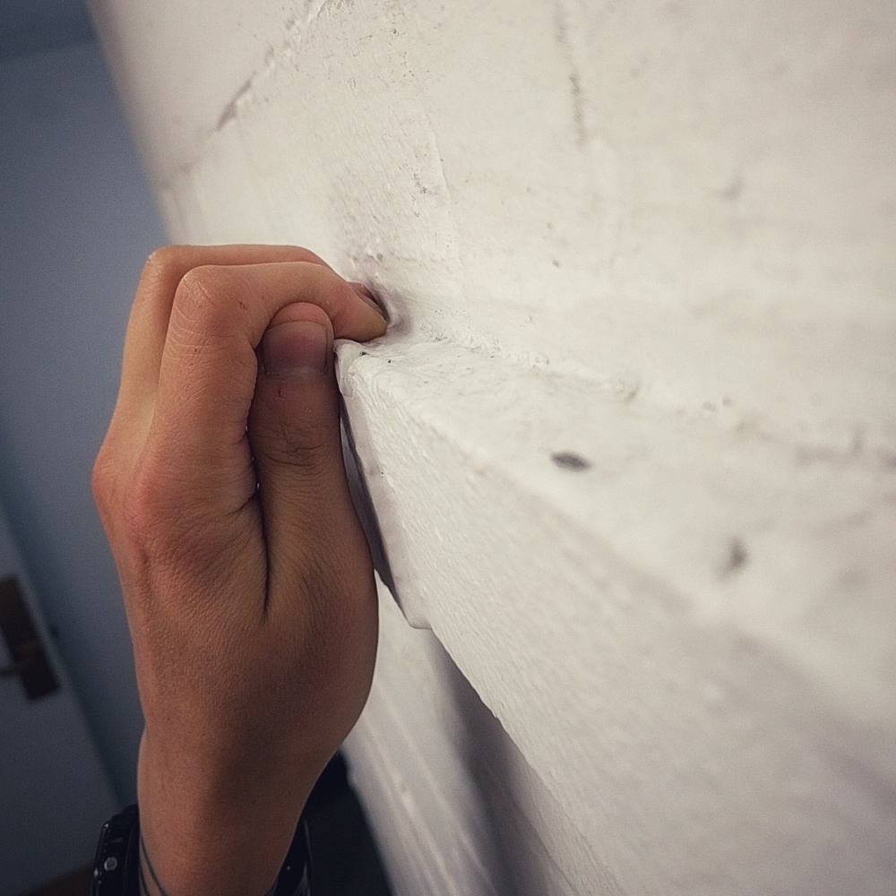 close-up of my hand in a tight crimp position on the lip of a white painted brick ledge in a hallway