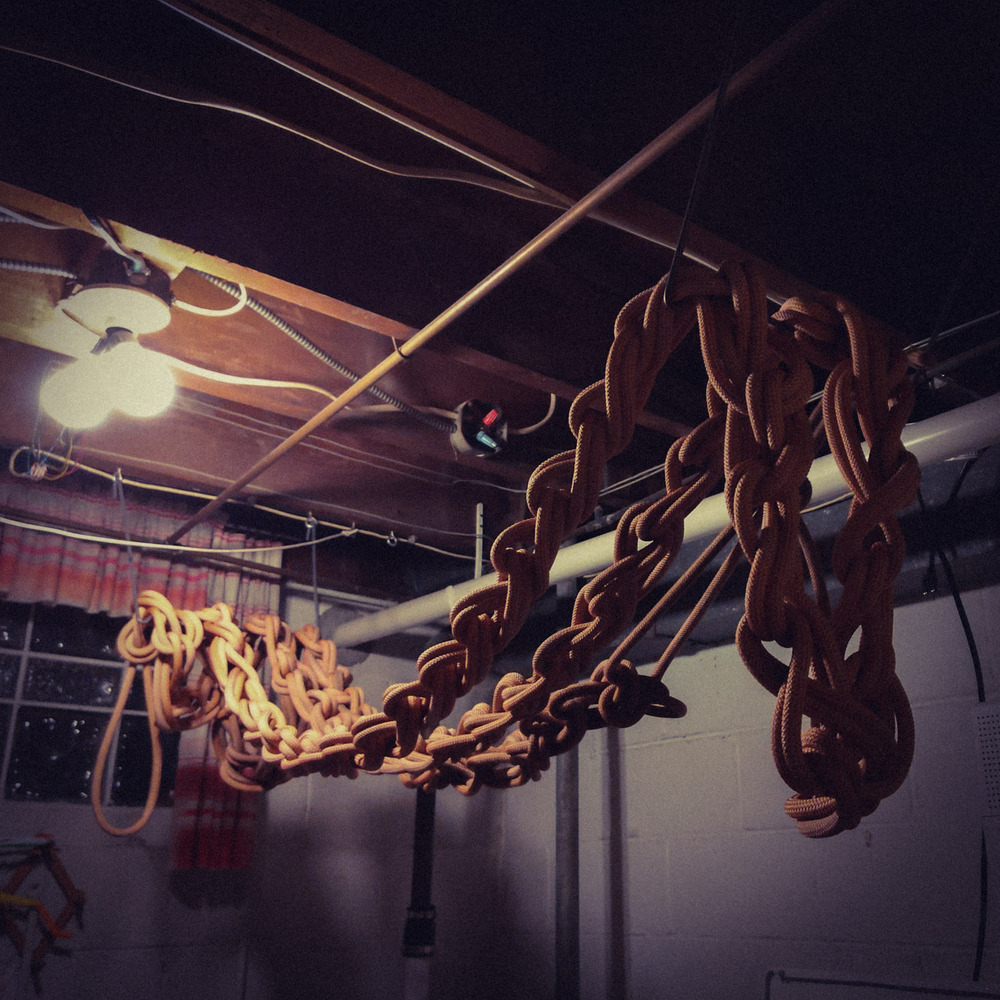 a monkey-chained climbing rope draped back and forth between a pair of wire racks in a basement, hanging up to dry