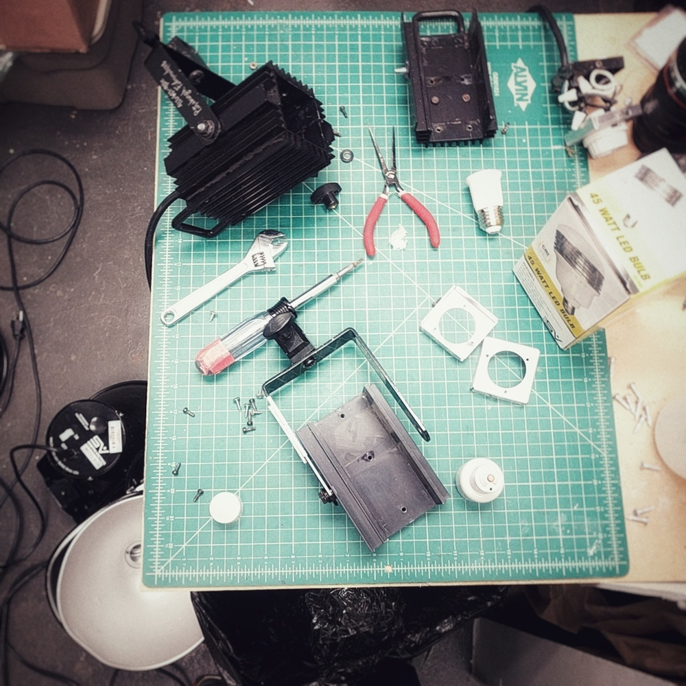 photo of my desk covered in several gutted studio lights, tools, bulbs, bolts, etc. scattered everywhere