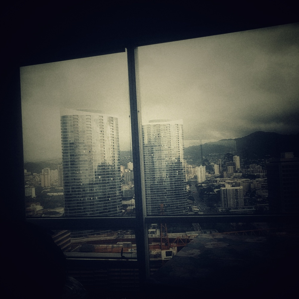 moody photo out of a large glass window overlooking honolulu, showing a pair of high-rise buildings, a large crane in a construction site, and sprawling smaller buildings creeping up the volcanic crater in the distance