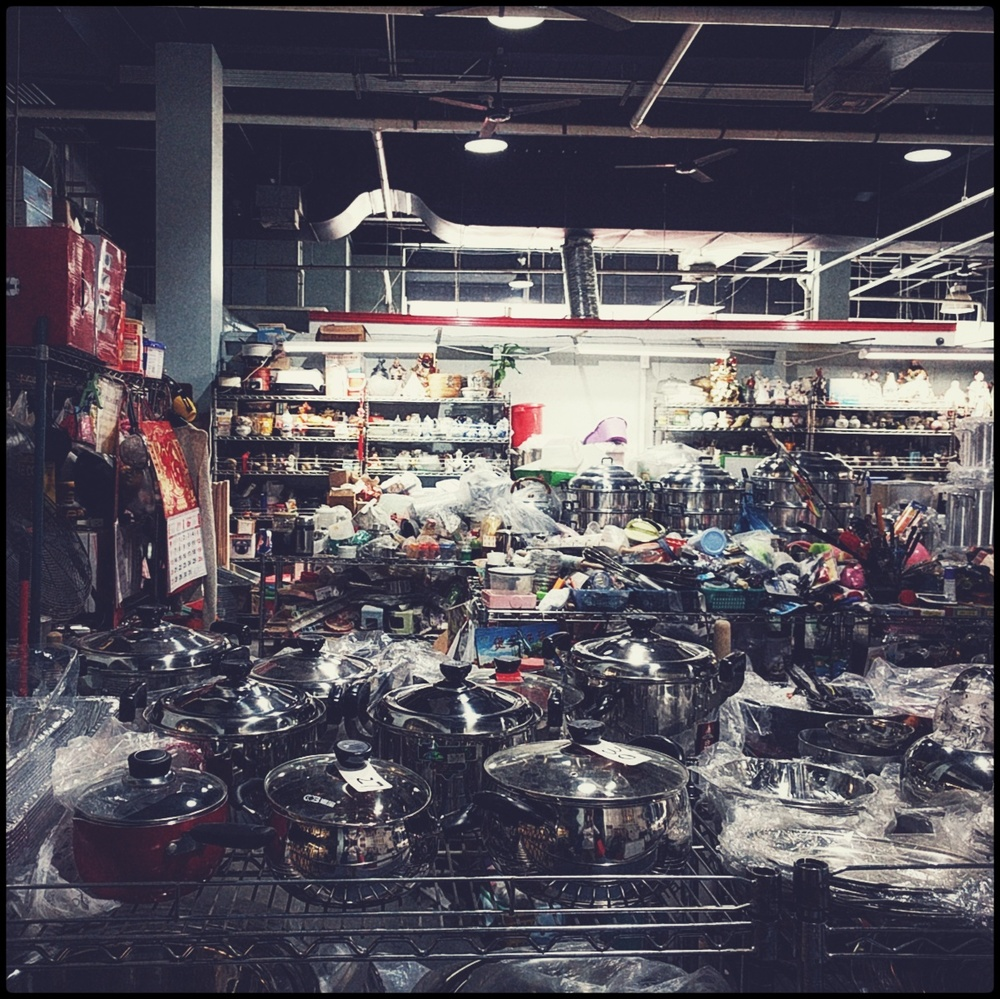 washed out color photograph of the inside of a kitchen goods market with lots and lots of pots and pans and other wares just piled up into the distance