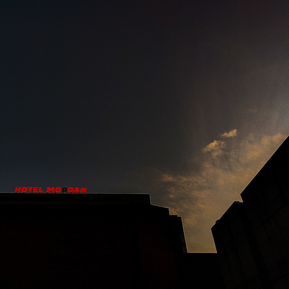 photo of a lit up metal sign for 'HOTEL MORGAN' on the roof of a building during sunset; the 'R' is out