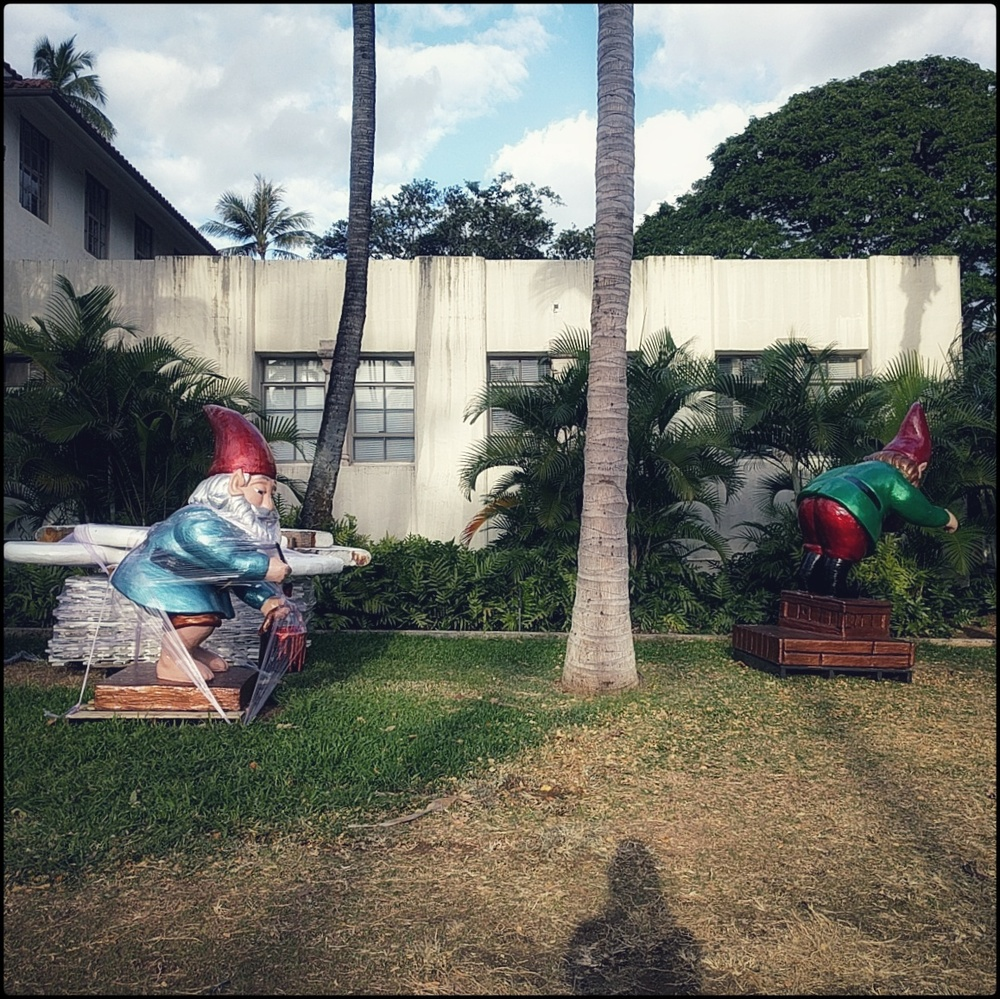 color photo of two large gnome statues in the middle of being packed up, one of them wrapped in plastic next to some palates, in an urban tropical setting