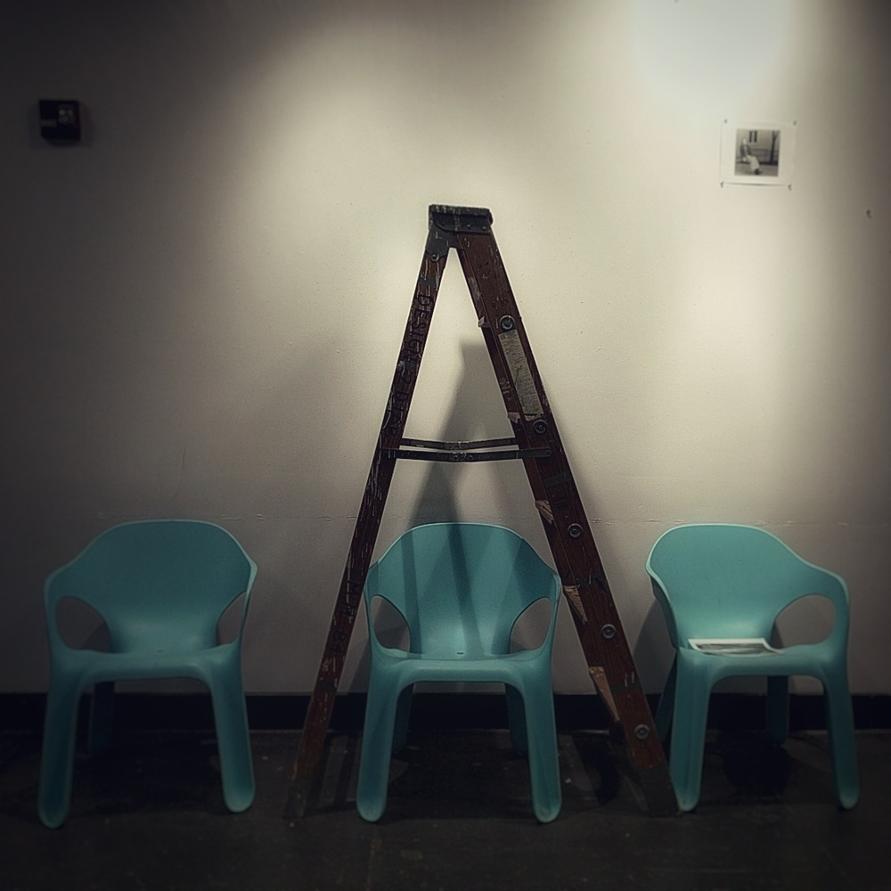 three blue chairs in a row against a blank wall; a wooden ladder is opened up and placed over the center chair.