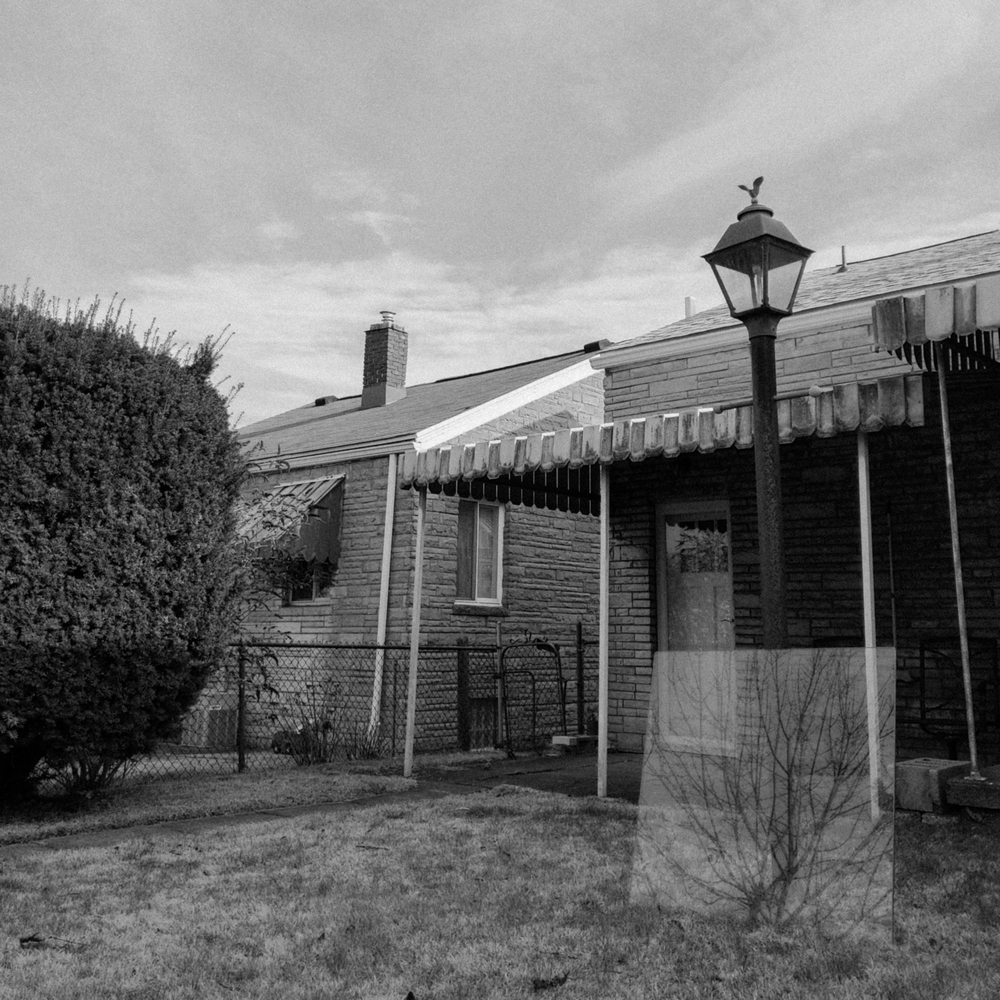 gritty black and white photo of the back of a house, showing a porch awning, a flat sky, a lamp post in the yard with a sheet of glass reflecting a tree.