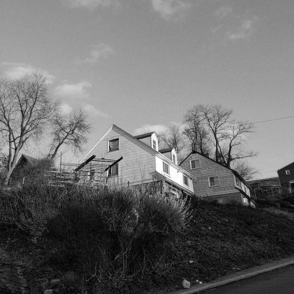 black and white photo of some houses on a hill and a big flat sky