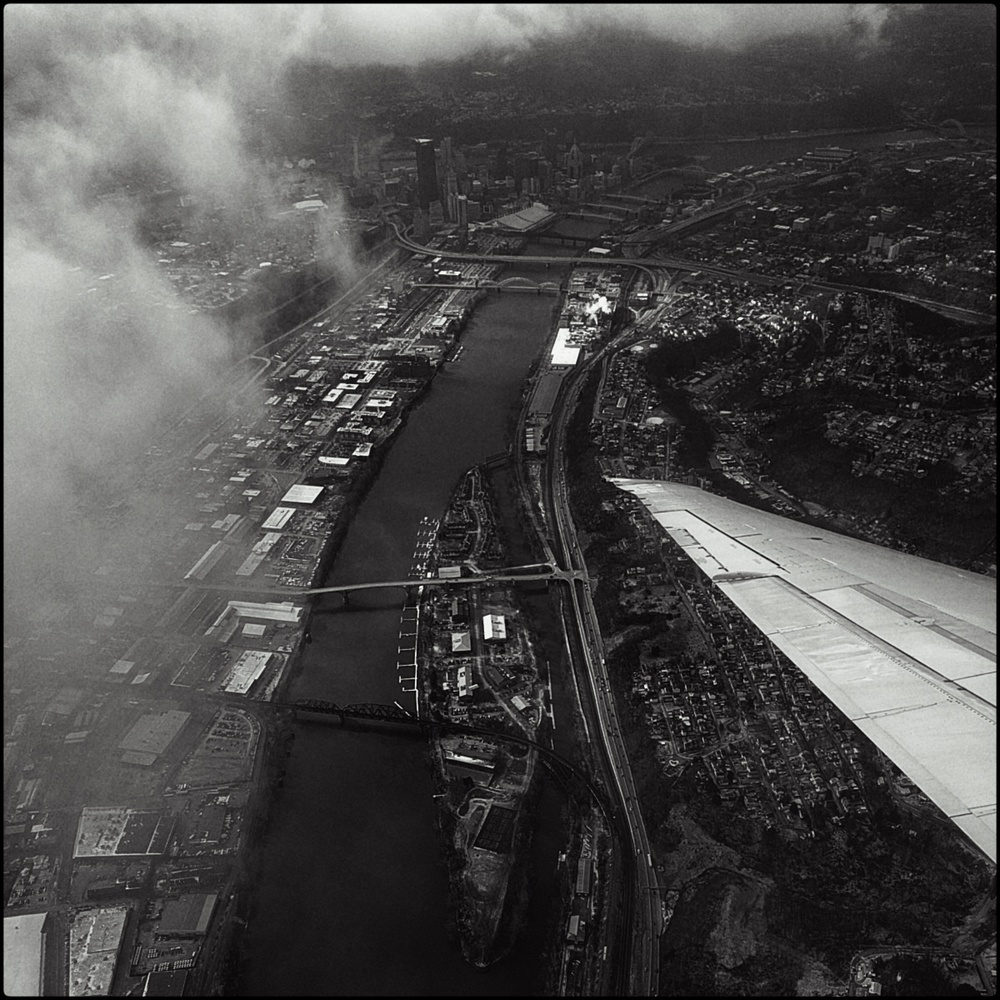 black and white photo out of a plane, showing the wing passing over downtown pittsburgh with some clouds