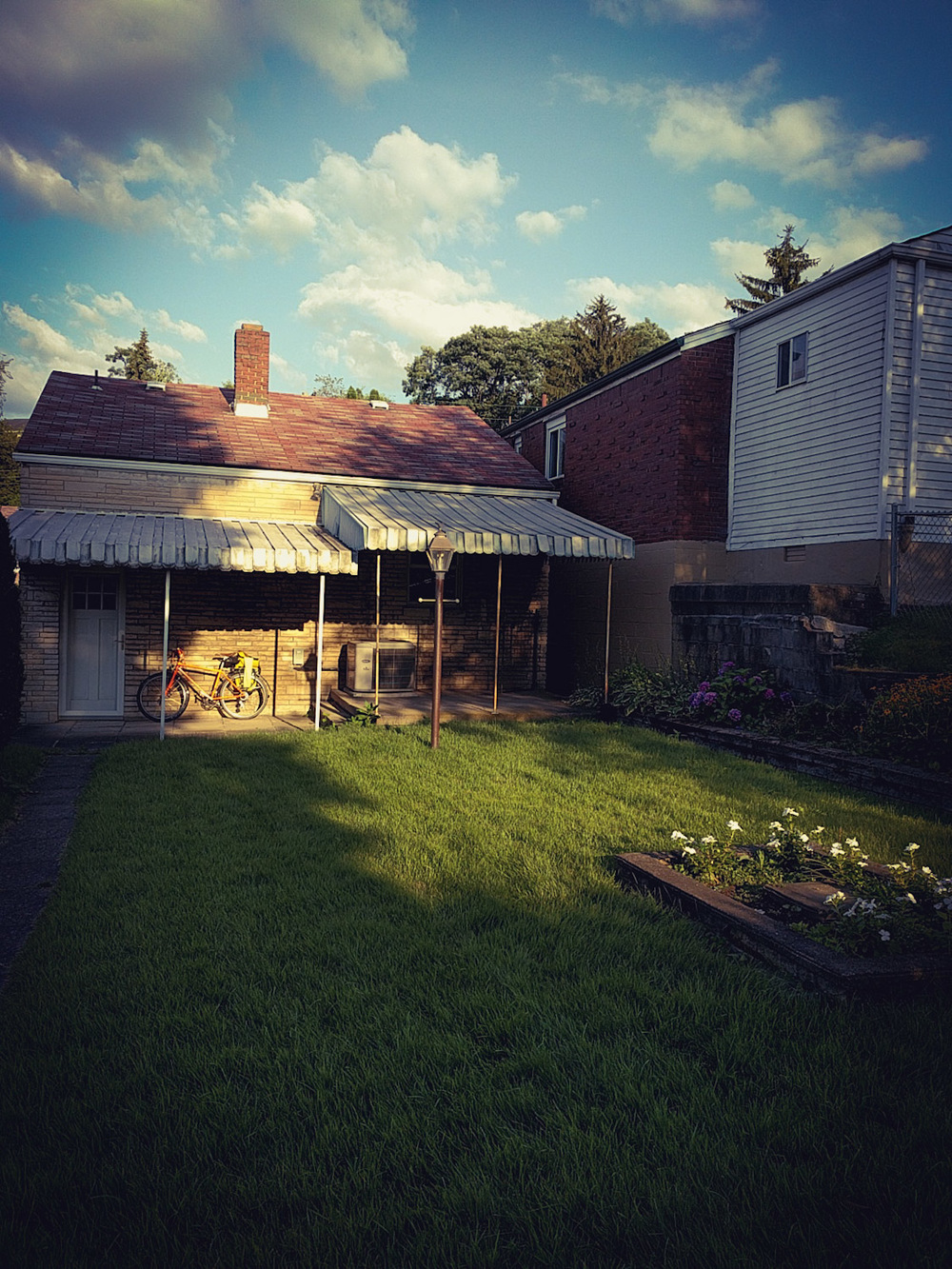 photo of a tidy little backyard near sunset with a long tree shadow and a bicycle parked under the porch awning